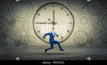 Businessman in suit running on time. Jump over clock sketch surrounded by gears cog wheels. Business time management concept. - Stock Photo