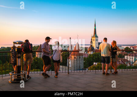 Baltic light city, view of tourists gathered on a terrace on Toompea Hill in Tallinn to watch the sunset over the medieval Old Town quarter, Estonia. - Stock Photo
