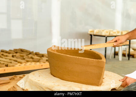 Male sculpture working carefully on his sculpture in an atelier. - Stock Photo