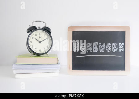 Alarm clock on a pile of books next to a blackboard with the text HOMEWORK wrote on it. Empty copy space for Editor's text. - Stock Photo