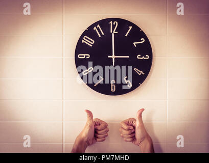Big black clock on white wall. Time change. DST. Survey of the European Union on time change. Gesture of agreement. Thumbs up of Caucasian man. - Stock Photo