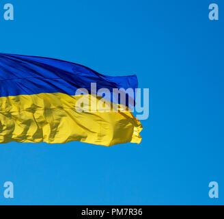 ukrainian textile flag develops against the blue sky, close up - Stock Photo