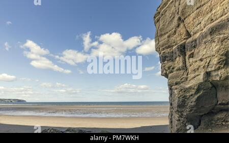 A wide stretch of water narrows as it runs to the sea across the beach.  A cliff face is in the foreground. - Stock Photo