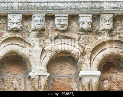 Arches and grotesque stone carvings on an external wall of the twelfth century norman church of St Peter, a grade 1 listed building, in the town of No - Stock Photo