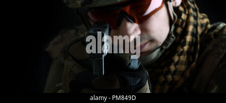 aiming at the camera focus on the muzzle of the gun. close up portrait of handsome military man. Macro shot on black background - Stock Photo