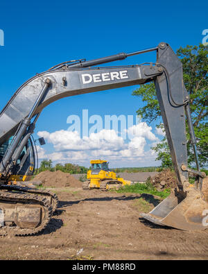 Heavy equipment sits at the ready to clear a new construction site. - Stock Photo