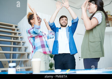 Portrait of three contemporary young people celebrating success and smiling cheerfully high fiving in modern office - Stock Photo