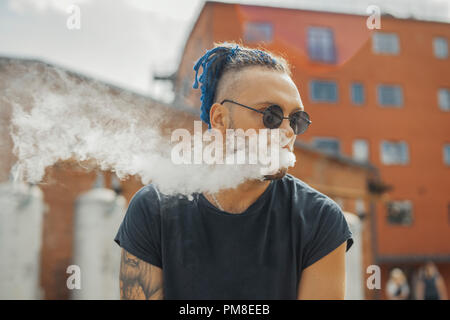 Portrait of young vaping man with dreadlocks. Vapor concept. Vaping e-Cigarette. Man is on foreground and focus, red bricked building is on background - Stock Photo
