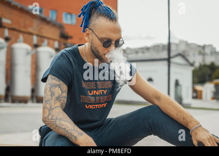 Portrait of young vaping man with dreadlocks. Vapor concept. Vaping e-Cigarette - Stock Photo