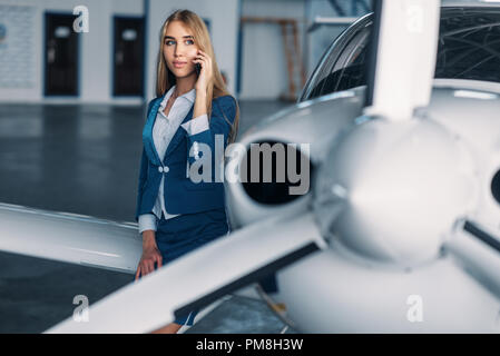 Attractive stewardess in uniform poses against propeller engine of small airplane in hangar. Air hostess in suit near plane. Private airline, flight a - Stock Photo