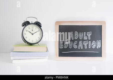 Alarm clock on a pile of books next to a blackboard with the text ADULT EDUCATION wrote on it. Empty copy space for Editor's text. - Stock Photo