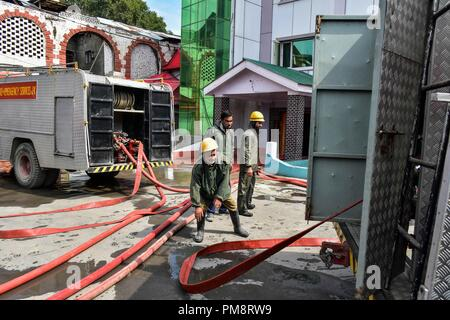 Firefighters seen at their trucks getting all equipment to extinguish the fire on the hotel building. A massive fire erupted at a local hotel here in Srinagar on Saturday, but there was no loss of life or injury according to police. Fire tenders were rushed to the spot and police, and fire and emergency services were trying to douse the flames. - Stock Photo