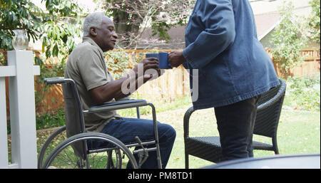 Disabled senior black man sitting in wheel chair - Stock Photo