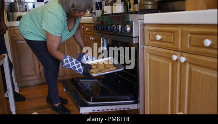 Mature African woman taking cookies out of the oven - Stock Photo