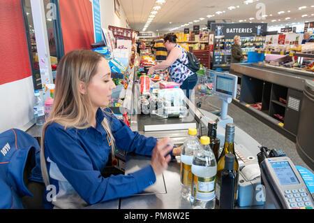 Female check-out counter worker in Aldi Supermarket, Gogmore Lane, Chertsey, Surrey, England, United Kingdom