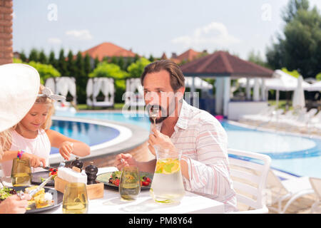 Nice handsome bearded man eating his food - Stock Photo