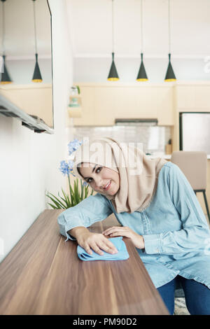 beautiful housewife wearing hijab cleaning wooden table in her h - Stock Photo