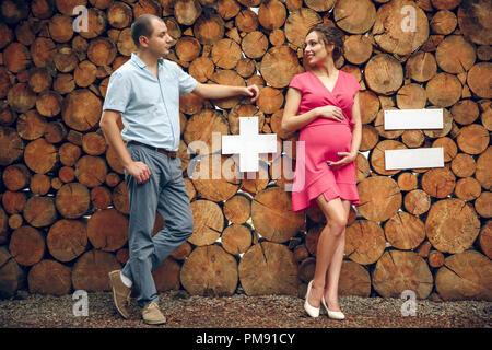 Couple in love pregnant cuddling, waiting for baby on wooden background. mathematical example - Stock Photo