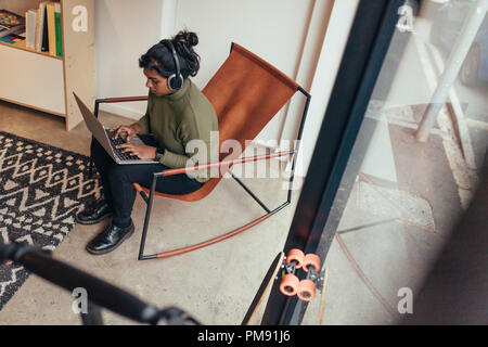 Young woman wearing headphones sitting on chair and working on laptop computer. Female computer programmer working at her startup office. - Stock Photo