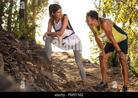Couple taking a break while running at mountain trail race. Fit man and woman taking rest and talking during a mountain race. - Stock Photo