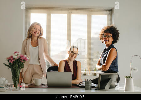 Three laughing businesswomen in casuals looking at camera. Group of successful businesswomen in office. - Stock Photo