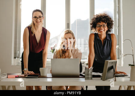 Portrait of smiling young businesswoman standing at desk and smiling at camera. Multiracial businesswomen in office. - Stock Photo