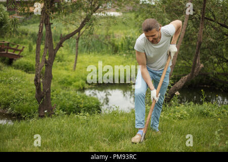 Smiling adult man planting a tree outdoors in park. - Stock Photo