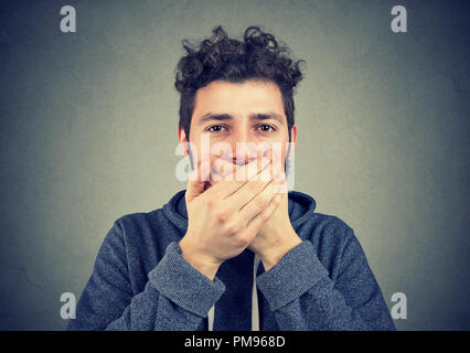 Young hipster man covering mouth keeping privacy and speaking no evil - Stock Photo