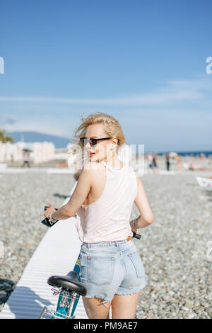 Woman leaning on the bicycle while standing near observation deck on the beach - Stock Photo