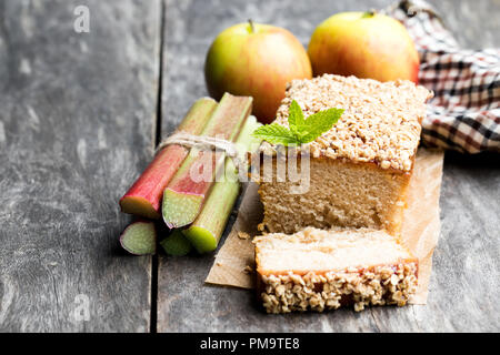 Homemade  rhubarb and apple cake topped with sweetened oats on wooden table - Stock Photo