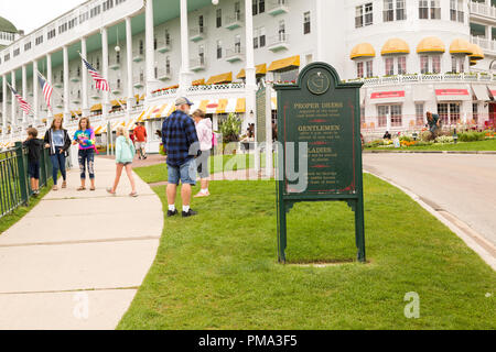 Outdoor sign with proper dress code rules, in front of the Grand Hotel resort on Mackinac Island, Michigan. The tourists  around are dressed casually. - Stock Photo