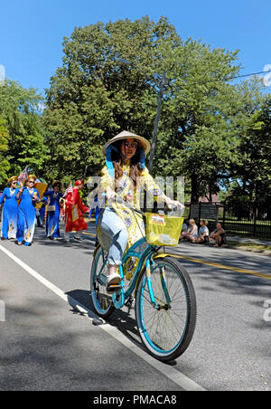 An American-Vietnamese woman rides her bike in the Parade of Flags, the official opening of the 73rd Annual One World Day in Cleveland, Ohio, USA. - Stock Photo