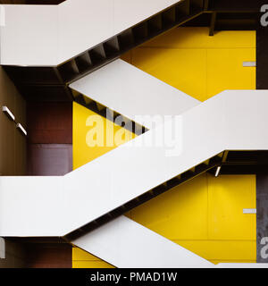 Modern stairs zigzagging up against a yellow wall in the atrium of a modern building in the city. Contemporary/ fashionable architecture & design - Stock Photo