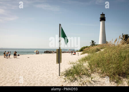 people walking on the beach overlooked by the Cape Florida Light, the oldest standing structure in Greater Miami, at Bill Baggs Cape Florida State Park - Stock Photo