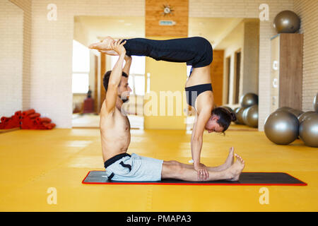 two sporty people practice yoga in pair fit couple doing