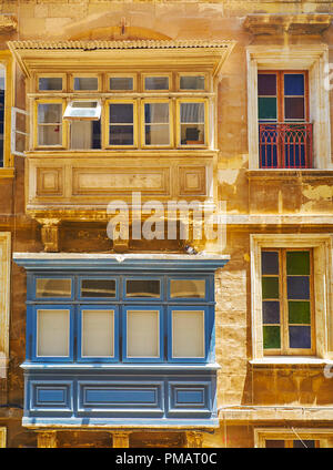 The stained-glass windows and colored wooden Maltese balconies of the old stone bulding, Valletta, Malta. - Stock Photo