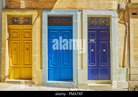 The West street boasts numerous historical buildings with traditional wooden doors, covered in bright colors, Valletta, Malta. - Stock Photo