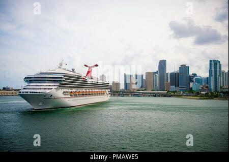 MIAMI, USA - CIRCA AUGUST, 2018: Carnival Victory cruise ship coming about to leave port with city skyline backdrop - Stock Photo