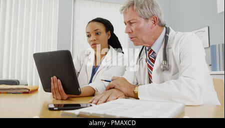 Black and Caucasian doctors working on a tablet in the office - Stock Photo