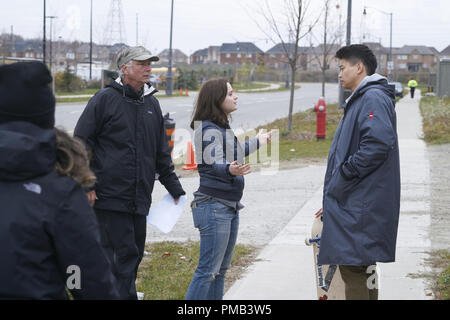 (l-r) Director John R. Leonetti and actors Joey King and Ki Hong Lee review a scene on the set of WISH UPON, a Broad Green Pictures release. (2017) - Stock Photo