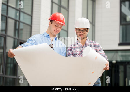 team of constructors are working according the plan and scheme - Stock Photo