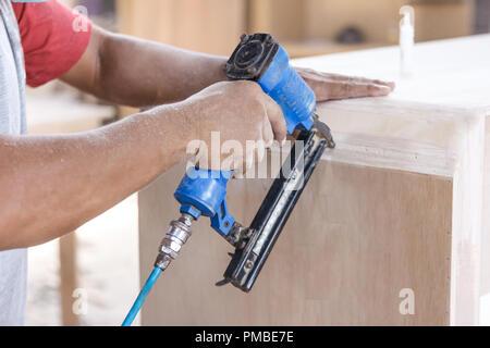 worker at carpenter workspace installing nail using pneumatic na - Stock Photo