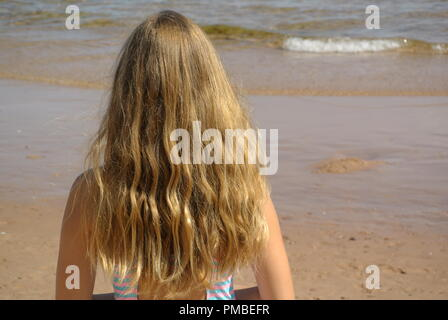 A close-up of a beautiful young girl with long blond and wavy beach hair standing on a beach and looking at the ocean on a sunny day, back view - Stock Photo