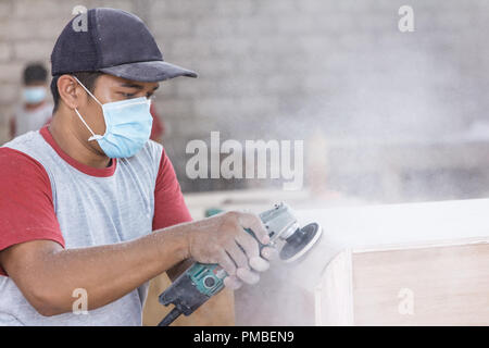 workers hands at carpenter workspace refining the surface of woo - Stock Photo