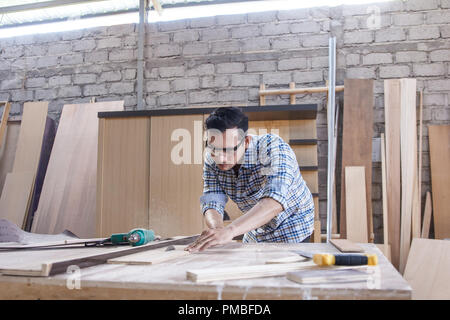 worker at carpenter workspace cutting the wood board using saw t - Stock Photo