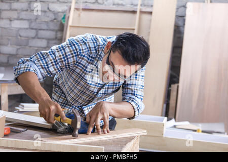 worker at carpenter workspace installing nail using hammer - Stock Photo