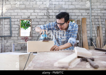 worker at carpenter workspace refining the surface of wood board - Stock Photo