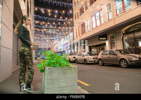 AUCKLAND, NEW ZEALAND - SEPTEMBER 14 2018; Auckland's Britomart area, bright and decorative lights, street furniture with young trendy woman  at night - Stock Photo