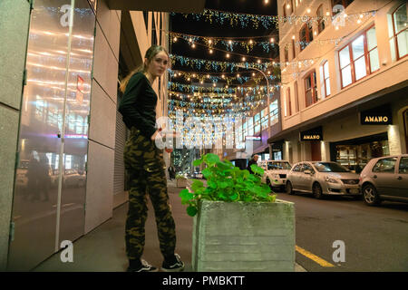 AUCKLAND, NEW ZEALAND - SEPTEMBER 14 2018; Auckland's Britomart area, bright and decorative lights, street furniture with defocused young trendy woman - Stock Photo