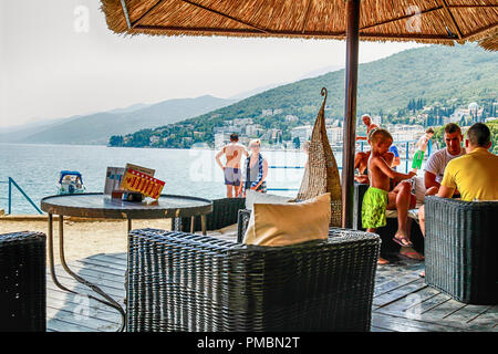 People sitting on the waterfront patio of a hotel bar in Opatija, Croatia - Stock Photo